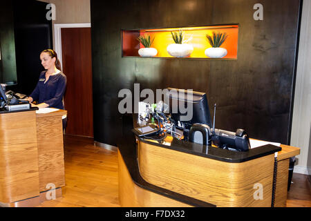 Stuart Florida Courtyard by Marriott motel hotel lobby front desk check-in reservations woman employee - Stock Photo