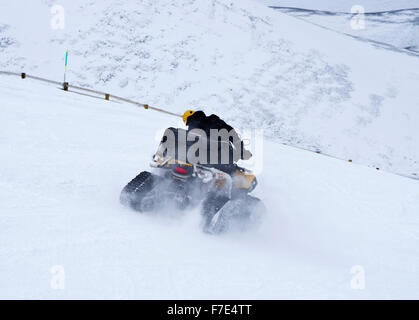 Quad bike with caterpillar tyres being driven down piste at Cairngorm Mountain Ski Centre, Scottish Highlands, Scotland - Stock Photo