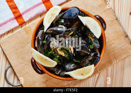 Mussels in a pot on the cutting board, lemons, tablecloth on wooden table