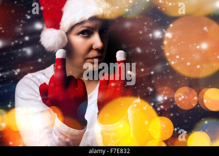 Christmas gift is late this year, young adult woman in Santa Claus costume showing middle finger, selective focus. - Stock Photo