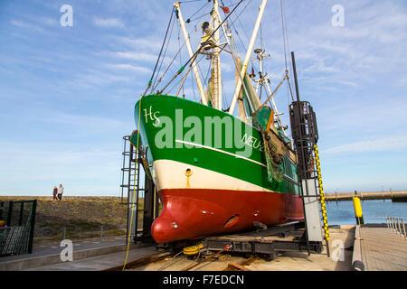 Shrimp trawler in a dry dock for maintenance, North Sea coast, Neuharlingersiel, Germany - Stock Photo