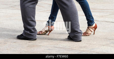 Couple dancing Tango at outdoor cafe in Spain. Woman wearing Jeans and heels; man wearing tracksuit and trainers. - Stock Photo