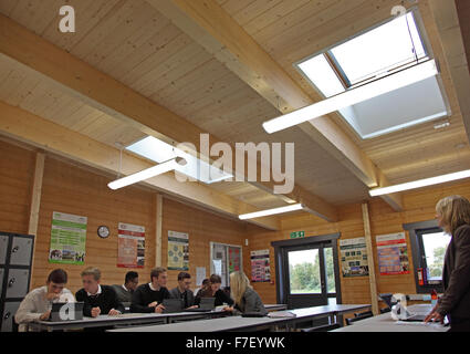 A sixth form IT class in progress in a new school built from timber - Stock Photo