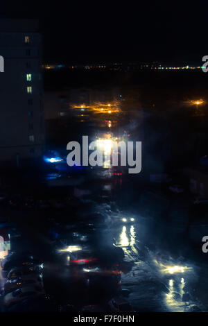 Car headlamps and street lights at night create bokeh style defocused blurs as rain water reflects off of windscreen - Stock Photo