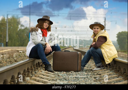 girls sitting with suitcase along the train tracks - Stock Photo