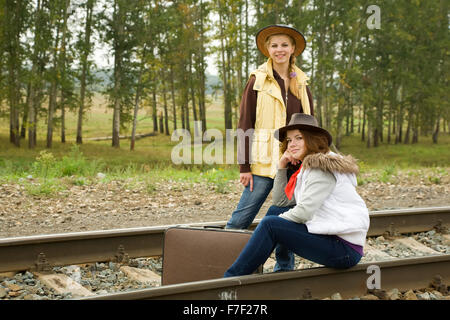 girls with suitcase walking along  railroad rail - Stock Photo