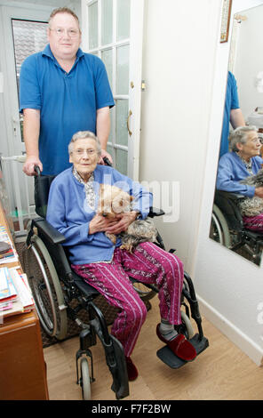 Male carer pushing an elderly woman in a wheelchair (could be mother & son) - Stock Photo