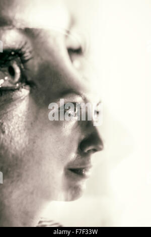 Monochrome double-exposure of a young woman's face and eyes blending her facial features twice - Stock Photo