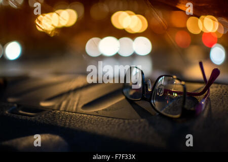 Pair of women's driving glasses sitting on a car dashboard at night with defocused car headlights in the background - Stock Photo