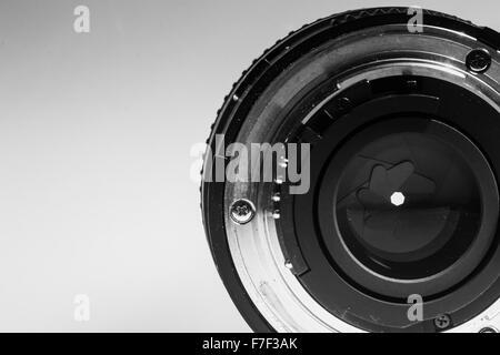 Close-up image of the rear end of a camera lens showing diaphragms and aperture rings in monochrome black and white - Stock Photo