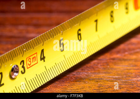 Single yellow metal outstretched measuring tape used for home DIY and industrial building tasks and projects. Nobody - Stock Photo