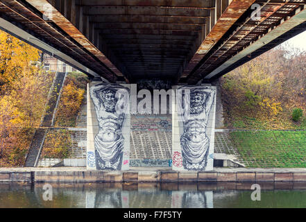 "Creative graffiti under a bridge over Neris river in Vilnius, Lithuania. Two painted Atlant statues ""holding"" a - Stock Photo"