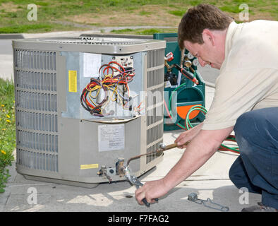 AC Repairman Welds Connector on Replacement Air Conditioning Unit - Stock Photo