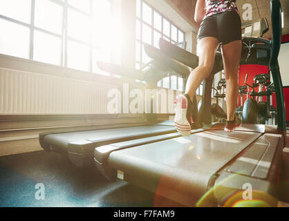 Rear view of woman in action running on treadmill. Focus on woman legs exercising on treadmill at the gym. - Stock Photo