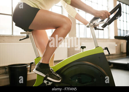 Cropped shot of fitness woman working out on exercise bike at the gym. Female exercising on bicycle in health club, - Stock Photo