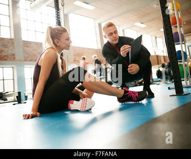 Personal trainer helping young woman on her work out routines in gym. Female sitting on floor with her personal - Stock Photo