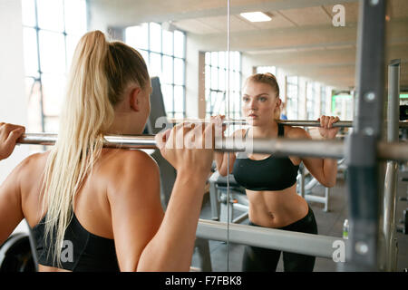Muscular caucasian blond woman in a gym doing squats with a barbell on her shoulders while looking at mirror. Young - Stock Photo