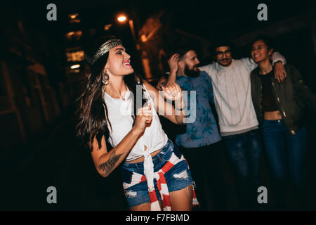 Portrait of pretty young woman dancing with her friends in background. Happy young female enjoying in a party with - Stock Photo