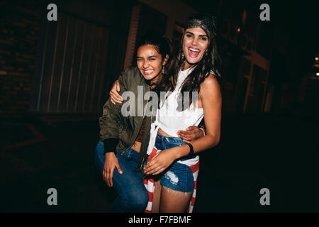 Portrait of two young female friends having fun outdoors. Women enjoying in outdoor party in evening. - Stock Photo