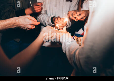 Close up shot of sparklers in hands of young people. Best friends celebrating new year's eve holding sparklers, - Stock Photo