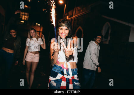 Portrait of cheerful young woman holding a sparkler and showing victory sign. Young people celebrating 4th of july - Stock Photo