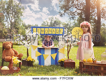 Two little kids are selling lemonade at a homemade lemonade stand on a sunny day with a price sign for an entrepreneur - Stock Photo