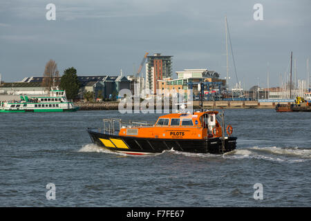 Orange and Black pilot boat crossing Portsmouth harbour at speed. Gosport ferry can be seen in the background. - Stock Photo