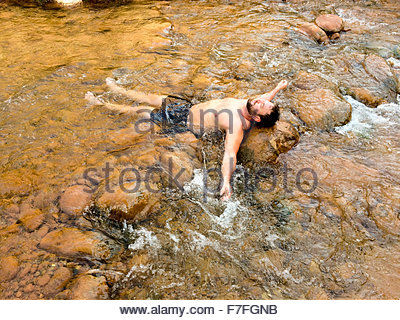 Mid 30's man male cools off in Bright Angel Creek at Phantom Ranch after hiking down the North Kaibab Trail, Grand - Stock Photo