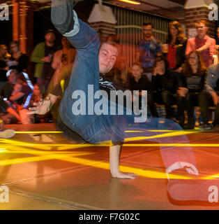 A young break dancer performs on a stage at a break dance competition. - Stock Photo