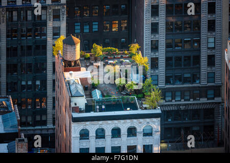Aerial view of a Manhattan rooftop in the heart of New York City. Roof garden in Chelsea with sunlit trees and wooden - Stock Photo