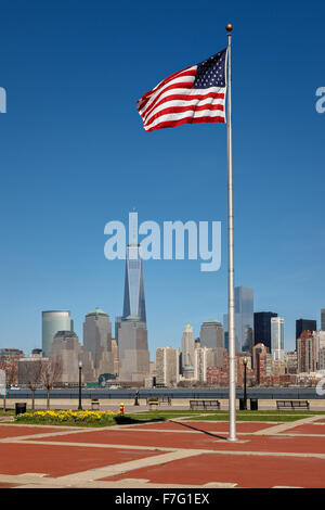 American flag standing tall in Liberty State Park, New Jersey, with a view of Lower Manhattan skyscrapers, New York - Stock Photo