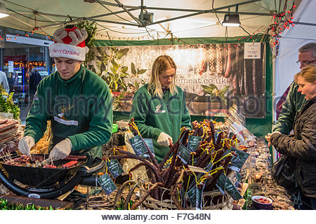 Customers at a wild meat stall at the Christmas Fair in Bury St Edmunds, Suffolk, England, UK - Stock Photo
