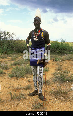Hamar man with painted legs, ostrich-feather hairdo and a stool in his hand posing for a photograph in South Omo, - Stock Photo