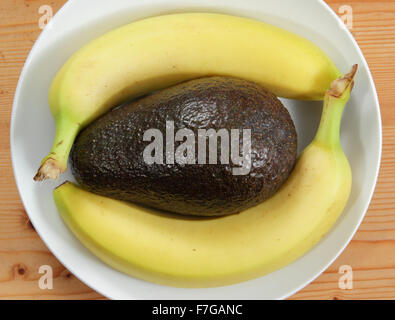 An avocado and bananas in a white porcelain bowl on a wooden background - domestic setting, england uk - Stock Photo