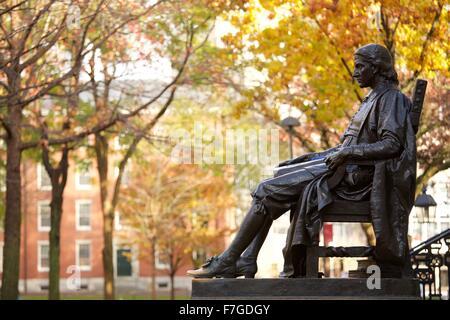 John Harvard statue in Harvard Yard in autumn, fall in Cambridge, Massachusetts. - Stock Photo
