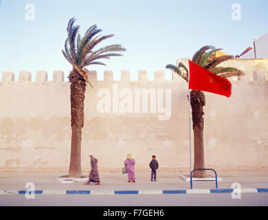 A Moroccan muslim man walks briskly past the city walls on his way to morning prayers. Essaouira,Morocco - Stock Photo