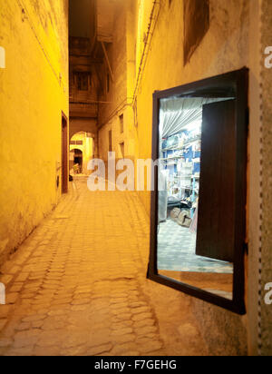 A mirror reflects a merchants store. In an alleyway in the Fes al Bali medina. Fes, Morocco, North Africa. - Stock Photo