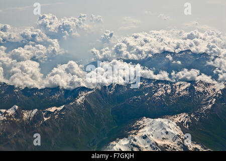 A photograph of several peaks in the Alps covered with snow and with thin clouds above - Stock Photo