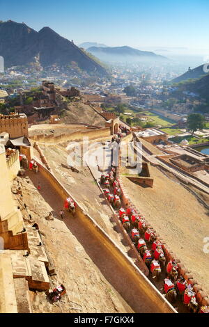 Elephants carrying tourists to the Amber Fort in Jaipur, Rajasthan, India - Stock Photo