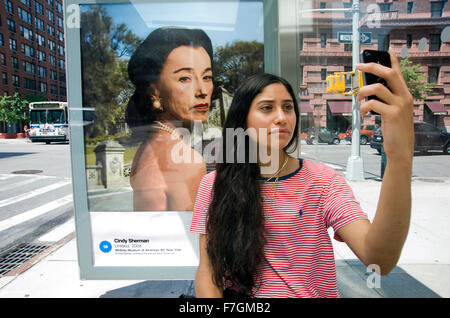 Young woman taking a selfie in front of a Cindy Sherman photograph reproduced on an outdoor advertising panel at - Stock Photo