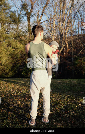 Man from behind holding baby boy - Stock Photo