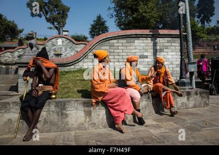 sadhus resting and chatting at Pashupatinath temple complex in Kathmandu, Nepal - Stock Photo