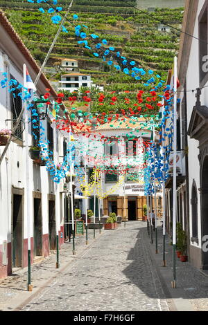 Street decorated with paper flowers on feast of Madeira Island, Camara de Lobos, Madeira, Portugal - Stock Photo