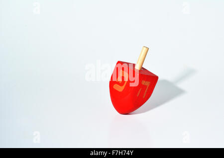 One Red Dreidel (sevivon) spin. It is a four-sided spinning top, played with during the Jewish holiday of Hanukkah. - Stock Photo