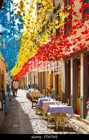 Street decorated with paper flowers on feast of Madeira, Funchal old town, Madeira Island, Portugal - Stock Photo