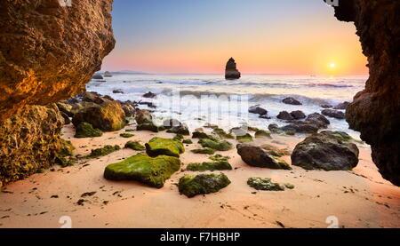 Sunrise at Algarve rocky beach near Lagos, Algarve, Portugal - Stock Photo