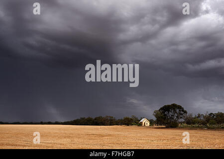Summer storm moves over harvested cereal crop. - Stock Photo