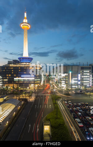Beautifully illuminated Kyoto Tower, city buildings and trailing car lights of traffic on downtown streets seen - Stock Photo