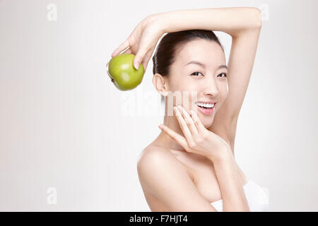 A smiling woman holding a green apple - Stock Photo