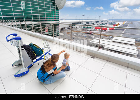 Young mother and little baby boy wait for boarding to flight in airport transit hall and looking at airplane near - Stock Photo